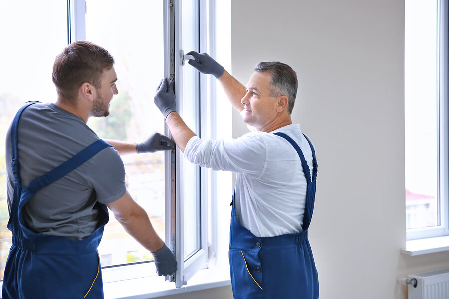 Two male workers installing a thermal glass window whilst wearing gloves