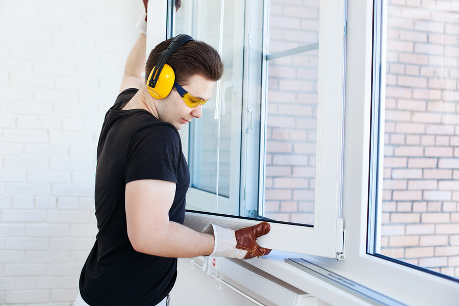 Male worker mounting a window on a balcony whilst wearing gloves