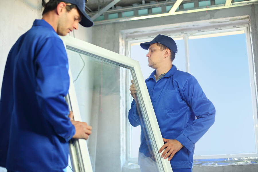 Two workers in blue coveralls set a new window in the window frame
