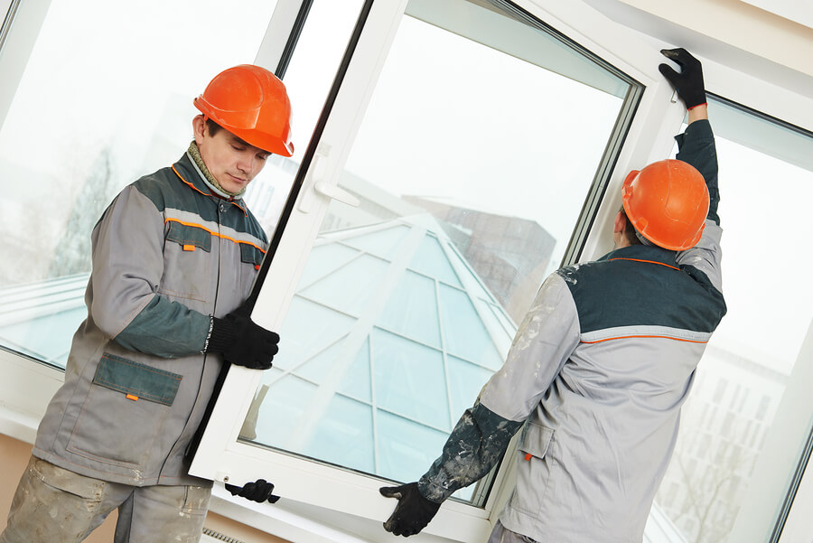 Two male commercial emergency glass repair workers installing a window